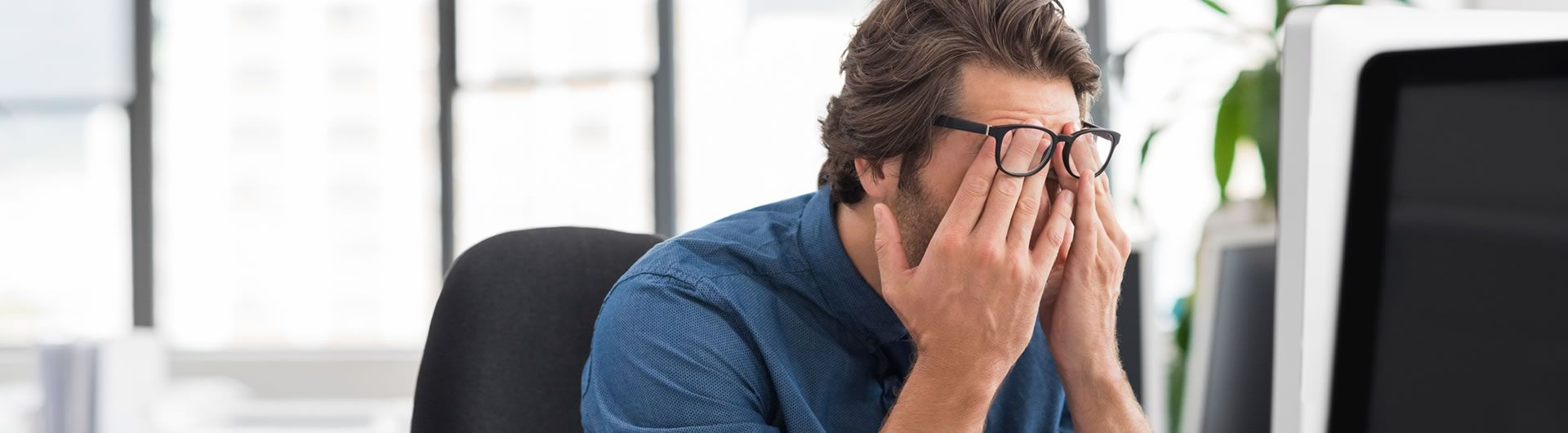 Man at computer stressed at work